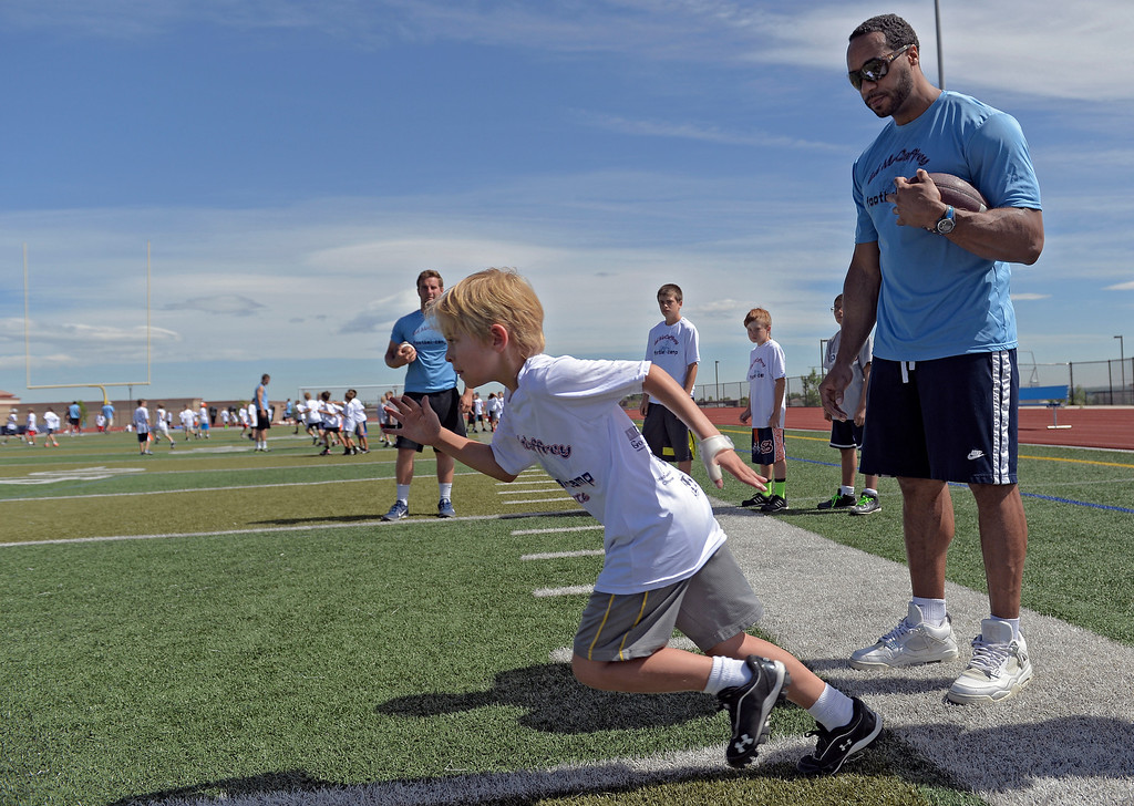 """. Former Broncos RB Kyle Johnson helps out during The Ed McCaffrey \""""Open\"""" Football Camp June 25, 2013 at Valor High School.  (Photo By John Leyba/The Denver Post)"""