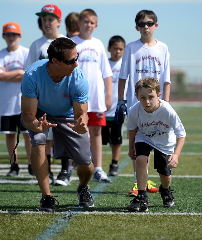 """. Trainer Loren Landow works with Logan Cass 10, of Parker during The Ed McCaffrey \""""Open\"""" Football Camp June 25, 2013 at Valor High School.   (Photo By John Leyba/The Denver Post)"""