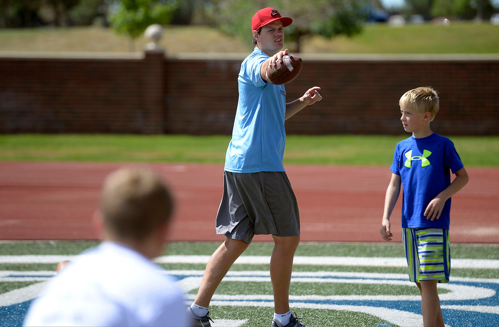 """. Miami Dolphins quarterback Aaron Corp helps out the quarterbacks during The Ed McCaffrey \""""Open\"""" Football Camp June 25, 2013 at Valor High School.  (Photo By John Leyba/The Denver Post)"""