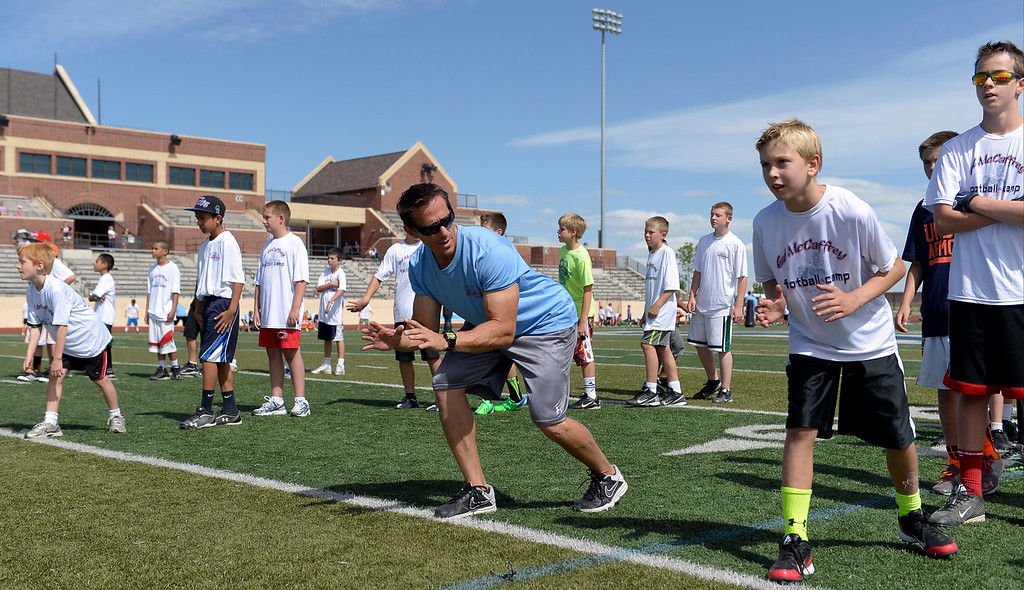 """. Trainer Loren Landow helps out during The Ed McCaffrey \""""Open\"""" Football Camp June 25, 2013 at Valor High School. Former Broncos star receiver Ed McCaffrey and other former pro football players conduct a football camp for kids ages 8-15 at Valor Christian High School. (Photo By John Leyba/The Denver Post)"""