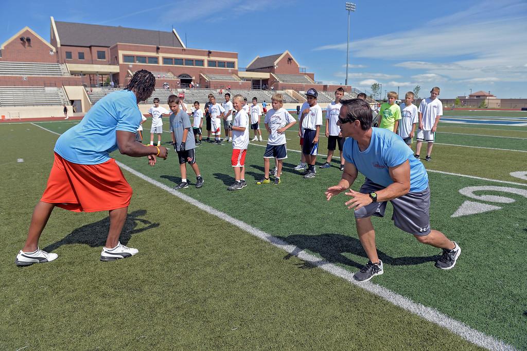 ". Loren Landow (R) helps out coach Jesse Jones during  The Ed McCaffrey \""Open\"" Football Camp June 25, 2013 at Valor High School.   (Photo By John Leyba/The Denver Post)"