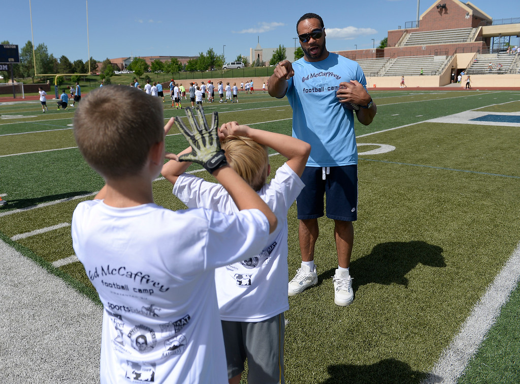 """. Former Broncos RB Kyle Johnson helps out during The Ed McCaffrey \""""Open\"""" Football Camp June 25, 2013 at Valor High School. Former Broncos star receiver Ed McCaffrey and other former pro football players conduct a football camp for kids ages 8-15 at Valor Christian High School.  (Photo By John Leyba/The Denver Post)"""