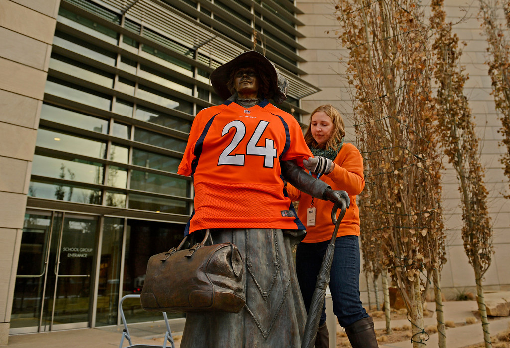 . Abby Krause, of the History Colorado Center, puts a Champ Bailey jersey on a bronze sculpture outside the museum in Denver, January, 10 2014. The Denver Broncos will take on the San Diego Chargers in the second round of the NFL playoffs on Sunday at Sports Authority Field at Mile High in Denver. (Photo by RJ Sangosti/The Denver Post)