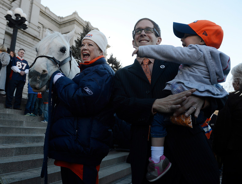 . Sharon Magness Blake, left, holds Denver Broncos mascot, �Thunder� as Colorado Speaker of the House, Mark Ferrandino, center, holds his daughter, Lila, out in front of the Colorado State Capitol for a small rally Friday morning, January 17, 2014. (Photo By Andy Cross / The Denver Post)