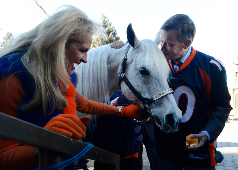 . Colorado Governor, John Hickenlooper, right, tries to coax the Denver Broncos mascot, �Thunder� into eating an apple next to the mascot\'s rider, Ann Wegener, left, on the west steps of the Colorado Capitol Friday morning, January 17, 2014 in celebration of Sunday\'s AFC Championship game against the New England Patriots. (Photo By Andy Cross / The Denver Post)