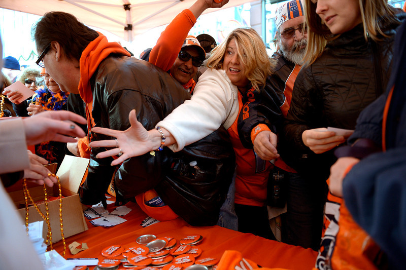. There was a small frenzy as fans reach for Bronco pins and towels as they gathered to show their support for the Denver Broncos at Denver Pavilions on the 16th Street Mall for their playoff run on as the team prepares to host the San Diego Chargers in an AFC Divisional Playoff Game. (Photo By Joe Amon/The Denver Post)