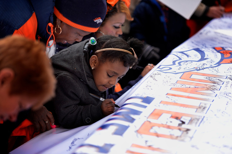 . 5 year old Kennary Milton is watched by her grandmother Rhodora Blanks as she writes on a huge sign that is hoped to be in the stadium for the next game as fans gathered to show their support for the Denver Broncos at Denver Pavilions on the 16th Street Mall for their playoff run on as the team prepares to host the San Diego Chargers in an AFC Divisional Playoff Game. (Photo By Joe Amon/The Denver Post)