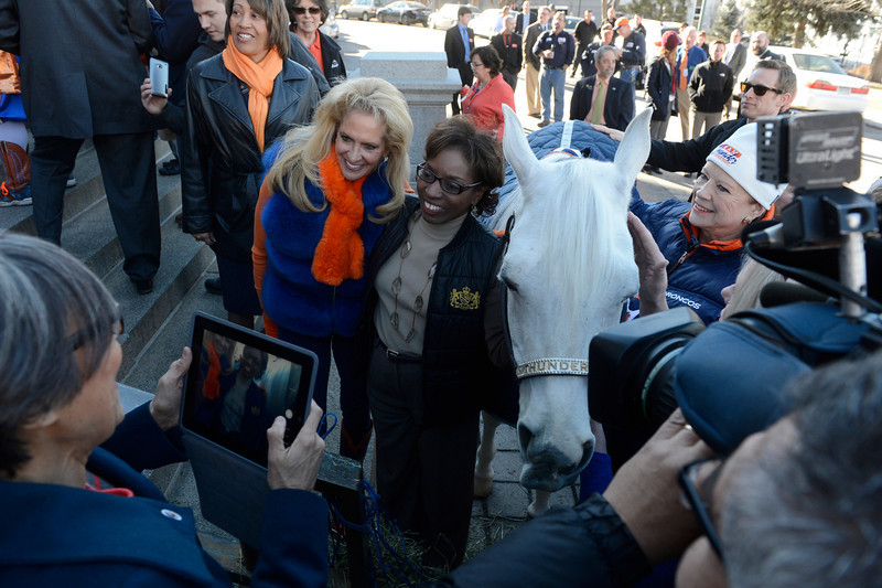 . Colorado Senator, Lucia Guzman, President Pro Tempore, D-Denver, lower right, takes an iPad picture of Ann Wegener, left, who rides Denver Broncos mascot, �Thunder� along with with Colorado Re. Rhonda Fields, center, with Thunder  on the west steps of the Colorado Capitol Friday morning, January 17, 2014 in celebration of Sunday\'s AFC Championship game against the New England Patriots. (Photo By Andy Cross / The Denver Post)