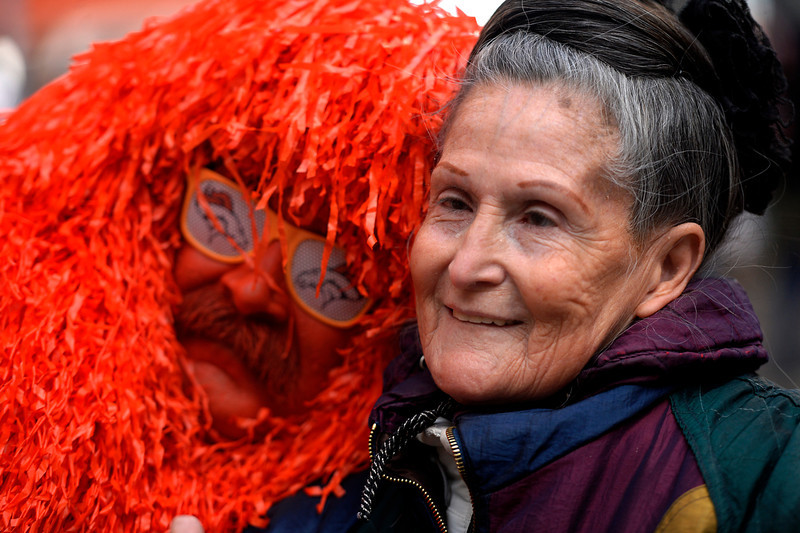 """. Kerry Green, on of the Mile High Monsters, poses with \""""The Bronco Lady\"""" 74 year old Penny Sandoval as fans gathered to show their support for the Denver Broncos at Denver Pavilions on the 16th Street Mall for their playoff run on as the team prepares to host the San Diego Chargers in an AFC Divisional Playoff Game. Sandoval usually wears a special Bronco hat that was at there last two super bowls. She says, \""""the hat will tell her if they are going to win.\""""(Photo By Joe Amon/The Denver Post)"""