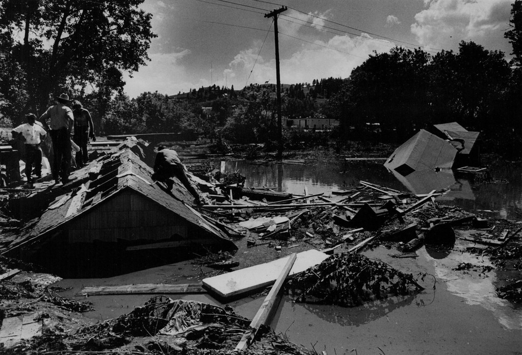 . JUN  12 1972  Rescue Workers look through roof of submerged rapid City house for flood victims. Civil defense officials estimate the missing at 500, and said it was impossible to estimate number of injured  (David Cupp/ The Denver Post)