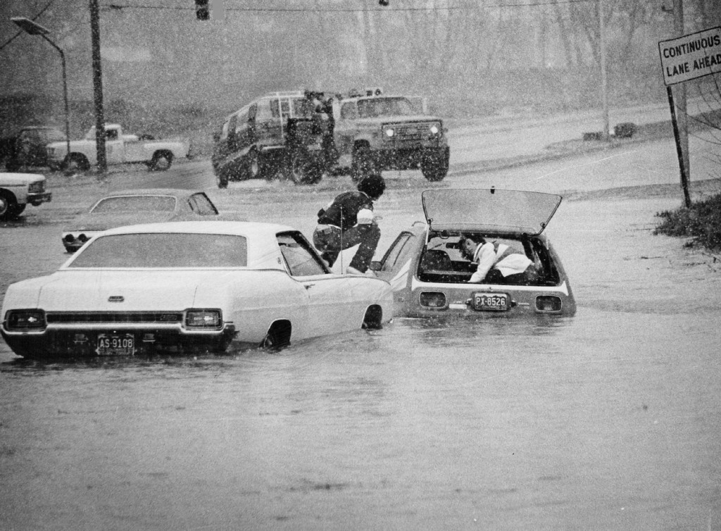 . MAY 3 1979  Donna Mallette waits in car at right to be rescued from flooded intersection in Aurora Her brother, Dale, on top of car at left, came to her rescue, but motorists in the background had to resort call to calling professional vehicle movers.   (Bill Johnson/ The Denver Post)