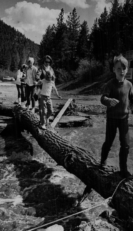 . MAY 9 1969 - Mrs. Darla Maly, in sunglasses, leads youngsters to Phillipsburg store across log bridge Makeshift span was hurriedly put up to replace one washed out by high water in Deer Creek Wednesday. From back to front: Cherie Waters, 16: Debbie Maly, 12; Nancy Waters, 18; Mrs. Maly; Dasha Maly 7; Dan Maly,9. (Bill Wunsch/ The Denver Post)