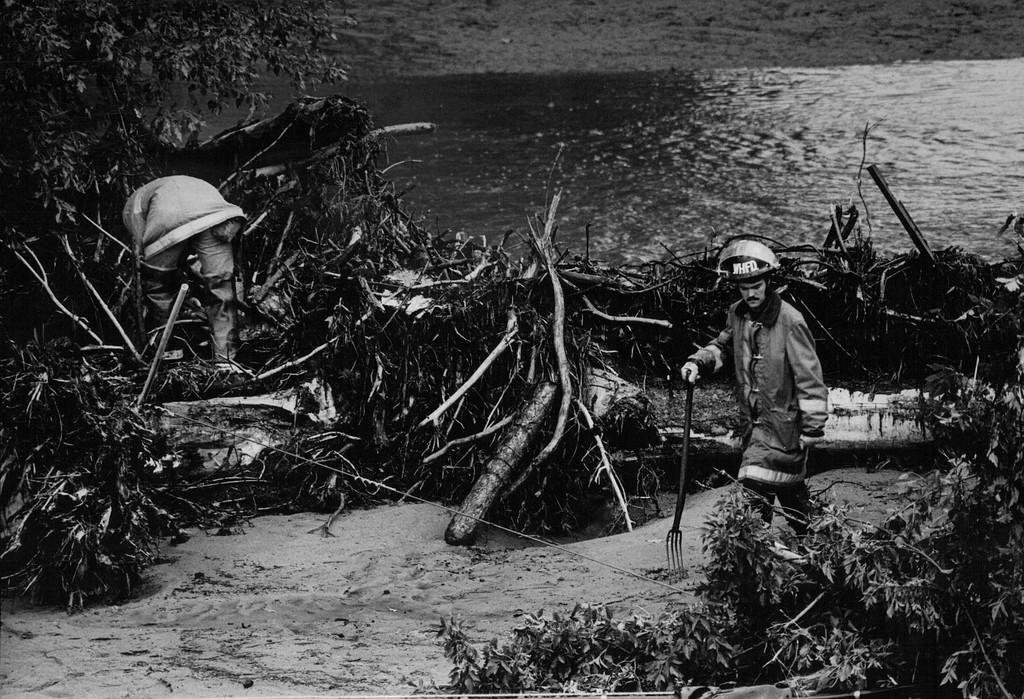 . AUG 2 1976  Loveland-area firemen search debris along the banks of the Big Thompson River for bodies of flood victims.  (Steve Larson/ The Denver Post)