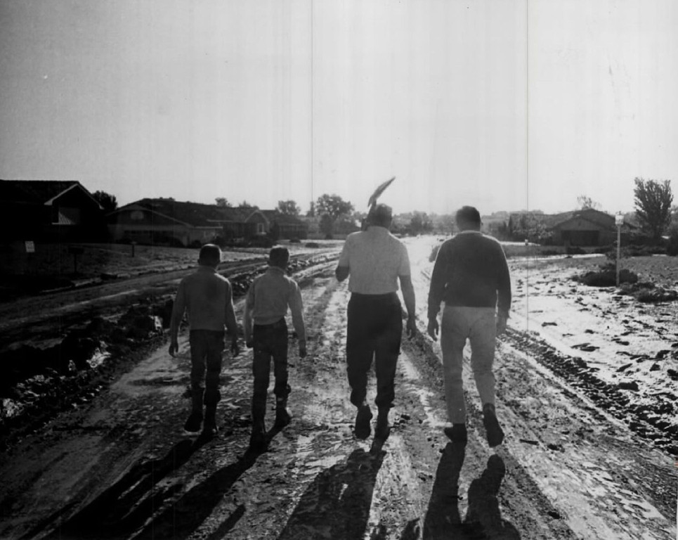 . JUN 3 1965  Mayor Robert Chase, with Shovel, of Columbine Valley Heads for cleanup work. The mayor\'s twin sons, David and Richard, 10, Gene Armstrong, right, walk with him toward river.  (Ira Gay Sealy/ The Denver Post)
