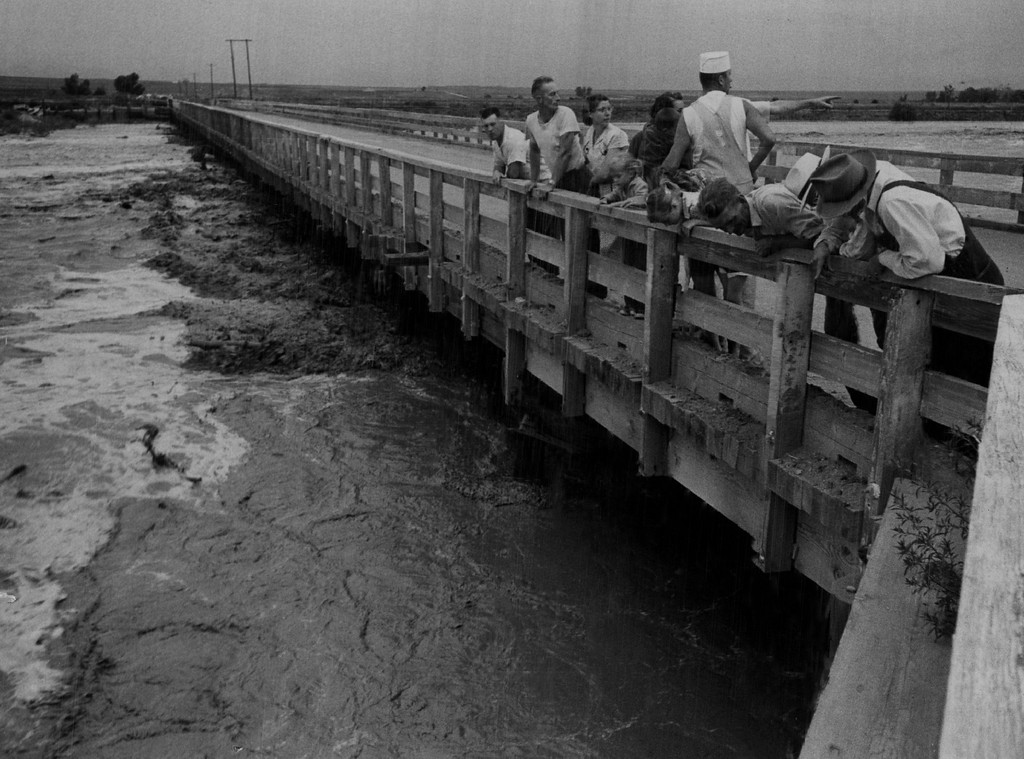 . 1957, JUL 27  Raging waters force closing of bridge over Cherry Creek Residents of the area stand on the 500-foot bridge over Cherry Creek along E. Belleview Ave. and watch the raging waters of the Creek reach highest stage in six years. The bridge was closed shortly after this picture was taken Friday for fear rushing debris might cause collapse.   (Dean Conger/ The Denver Post)