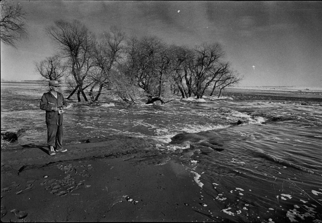 . FEB 10 1980  Weld County Resident Stands Amid Rushing water form prospect valley dam as it floods across farmland East/Northwest of the break.  (John J. Sunderland/ The Denver Post)