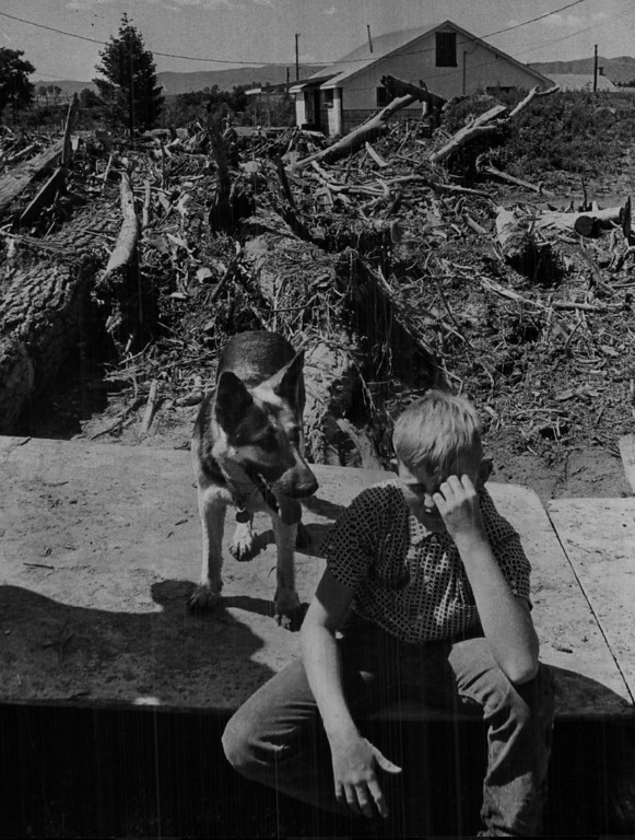 . JUN 23 1965  It\'s his home-or was before the flood Robin Borton, 11, turns his back on his debris-filled home, severely damaged in last week\'s flood on Plum Creek. His father, Robert Borton, said the proposed Chatfield Dam would inundate the property. But he favors the dam because it will avert any future disaster.  (David Mathias/ The Denver Post)