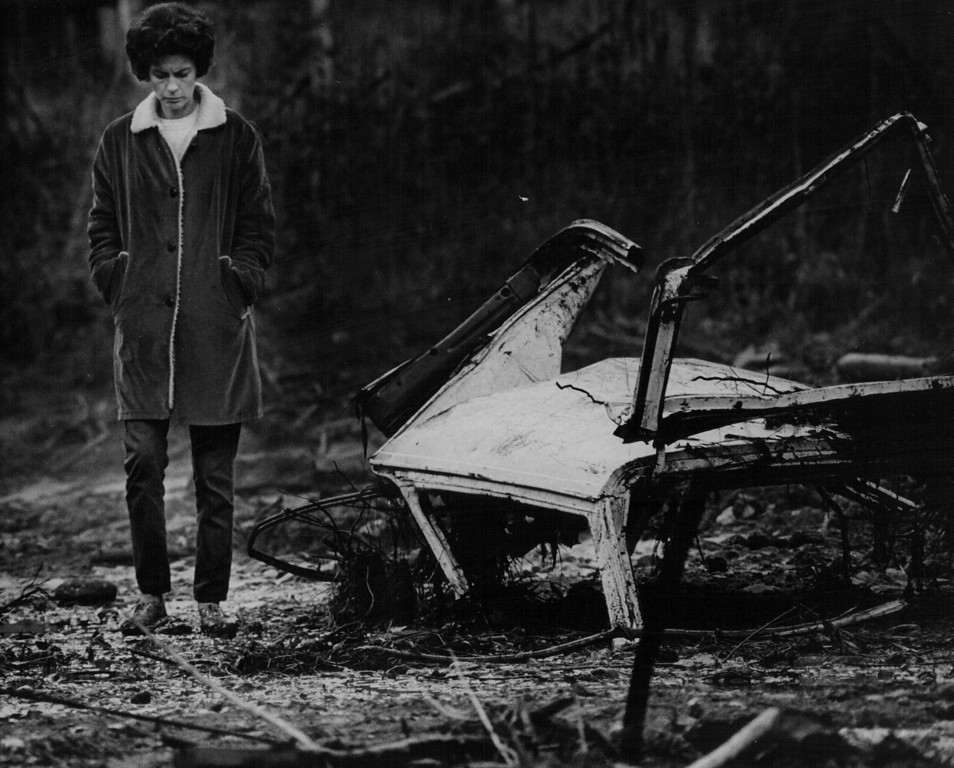 . AUG 5 1970  Mrs. Frank Wallic walks dejectedly past a pile of rubbish swept onto her property by flooding Parmalee Gulch. Her husband set damage at $8,000.  (Steve Larson/ The Denver Post)