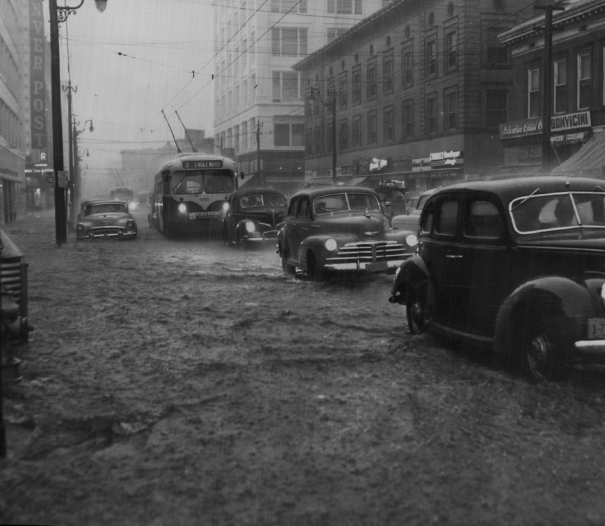 . 1953, JUL 9  Passenger cars and a tramway bus move cautiously along Fifteenth street, feeling their way through flood water which stretched curb-to-curb through the business district soon after the city was lashed by a cloudburst late Thursday. This photo was made at 4:45 p.m., soon after the vicious wind and rain storm broke with unprecedented fury and violence.  (Dean Conger/ The Denver Post)