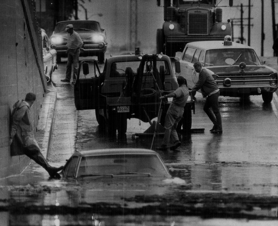 . JUN 8 1969  A wrecking truck begins to pull out a car stalled in high water beneath the Union Pacific Railroad overpass on 38th St. near Walnut St. Two cars were trapped by high water and policemen rescued on unidentified man, woman, boy from one of them.  (Steve Larson/ The Denver Post)