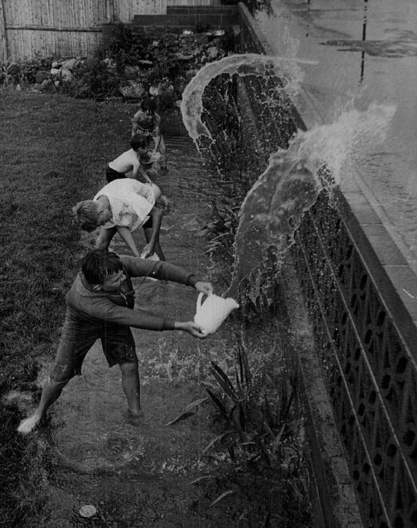 """. JUL 14 1967 - Adams county youngsters enjoy their \""""work. \"""" Not long before this photo was taken, water stood 18 inches deep in back yard of Herbert Klein, 7204 Santa Fe Drive. Trying to hasten runoff by throwing water into street are, from top, Mark Zimmer, Kevin Klein, Herbert Klein, Keith Howitt. (Bill Peters/ The Denver Post)  Top to bottom  Mark Zimmer, 8, 7205 Inca St.  Kevin Klein, 5, of 7204 Santa Fe. Drive. John Praml, 14, of 7214 Santa Fe. Drive. Keith Howitt, 13, of 7213 Santa Fe Drive. 7204 Santa Fe Drive home of Herbert Klein"""