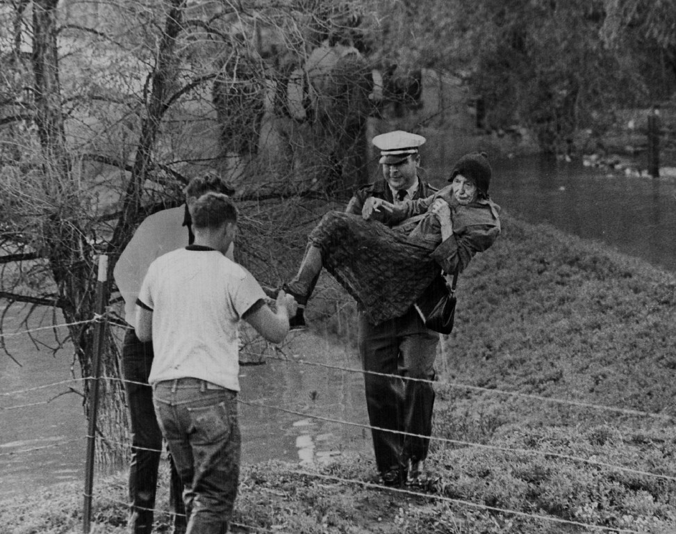 . JUN 16 1965 - Effie Nelson, 84, is carried from flooded home near Brighton. Eddie Krantz, a member of a rescue unit, rescues her from her farm home Thursday. (Duane Howell/ The Denver Post)