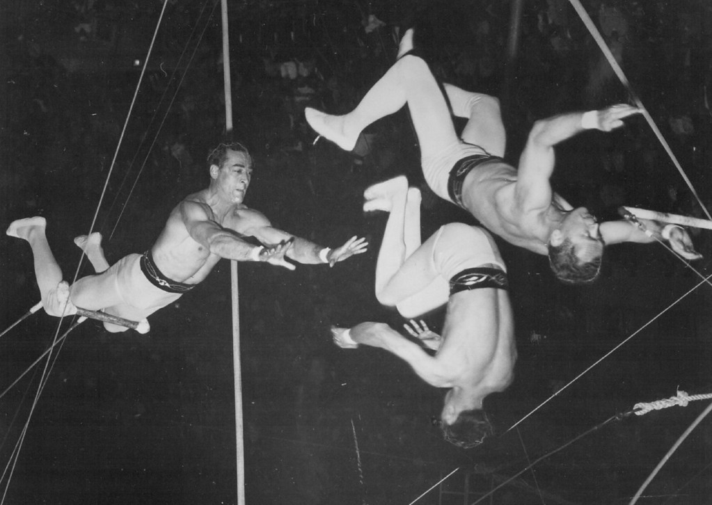 """. JUL 23 1961 - Those Daring Young Men - Here the Flying Comets, one of two expert flying trapeze troupes with Ringling Bros and Barnum & Bailey Circus, execute the \""""passing leap\"""". The catcher, right, is about to grasp the wrists of the top flyer after having just released the flyer at the left, who is returning to the \""""swing bar.\"""" (Denver Post digital archive photo)"""