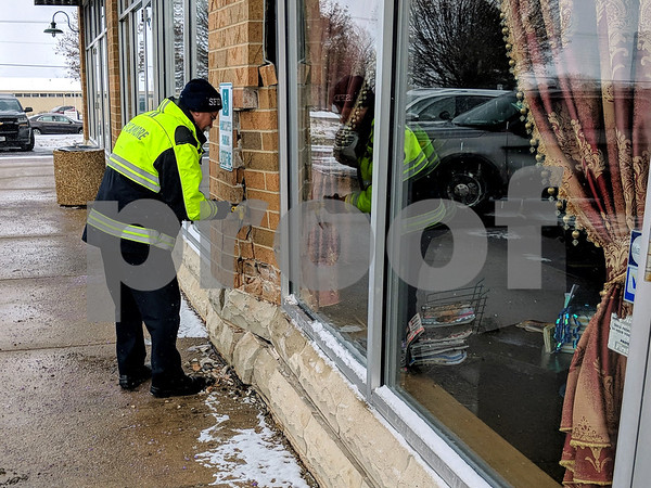 Sycamore Fire Chief Peter Polarek pries some of the damaged bricks from the wall to inspect behind the damage caused when a vehicle struck the wall Wednesday at Pro Nails, 1170 Dekalb Ave. in Sycamore . The driver had accidentally hit the gas pedal instead of the brake, police said. There were no injuries.