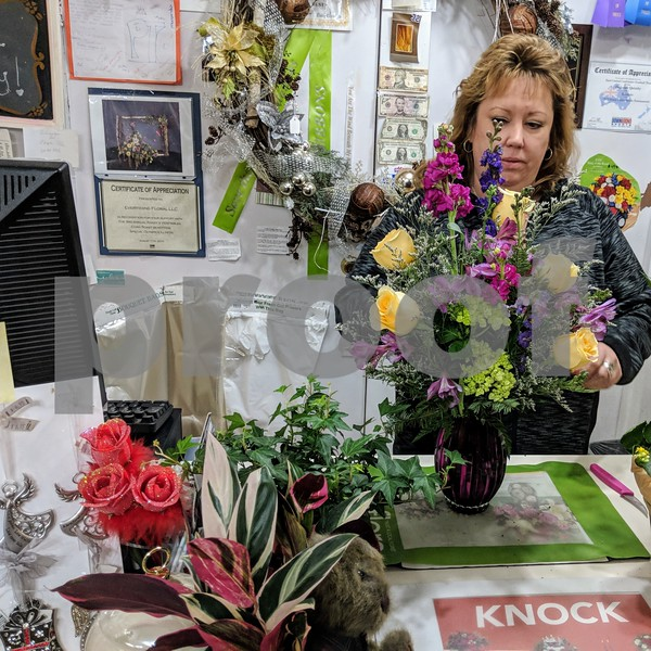 Debbie Heiman, owner of Everything Floral in Genoa, prepares a flower arrangement on Jan. 4. Heiman said Genoans have always rallied around one another during times of adversity, and the past 10 days have been nothing different.