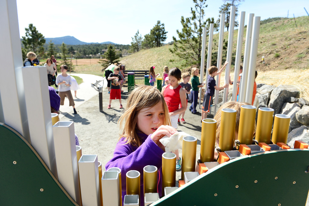 . EVERGREEN, CO - MAY 5: Grace Eye, 9, cleans off a set of chimes alongside her classmates from Montessori School of Evergreen during a service learning trip to Stagecoach Park on May 5, 2016, in Evergreen, Colorado. Evergreen Rotary donated the musical park, designed by Durango-based Freenotes Harmony Park, to Evergreen Park and Recreation District. (Photo by Anya Semenoff/The Denver Post)