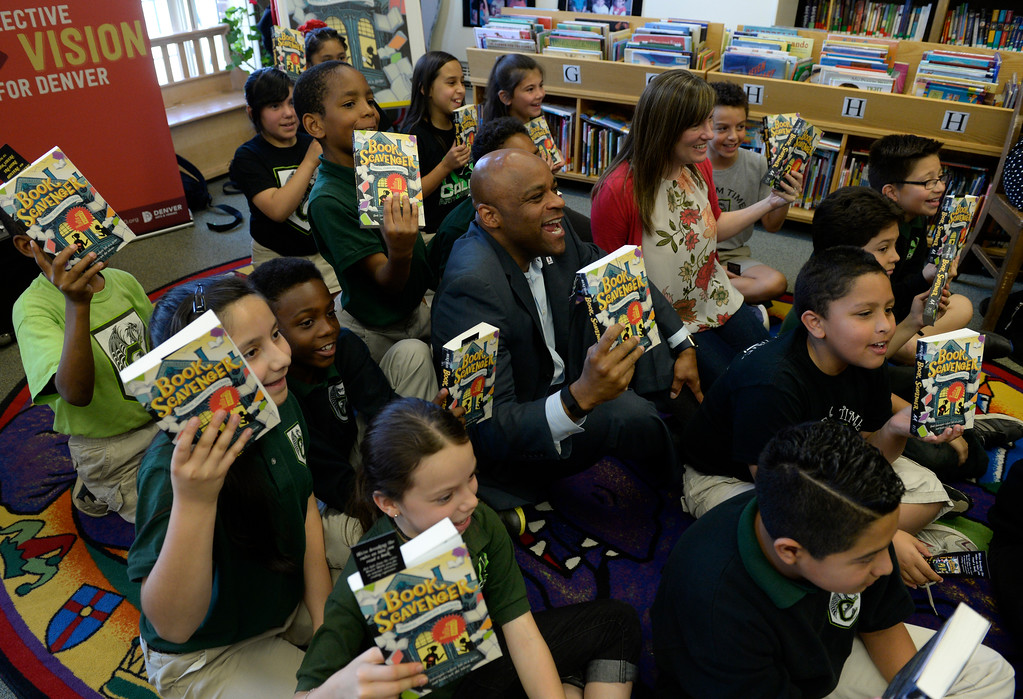 ". DENVER, CO - MAY 20: Denver Mayor Michael Hancock, center, and the book author, Jennifer Chambliss Bertman (floral blouse), join the students on the floor so the teachers can take a photo. The Mayor  introduced this year\'s Youth One Book, One Denver titled ""Book Scavenger\"" in the library at the Cole Arts and Science Academy on Friday, May 20, 2016. The author, Jennifer Chambliss Bertman and the Mayor signed a copy of the book for a group of fourth-graders in the library.  (Photo by Kathryn Scott Osler/The Denver Post)"