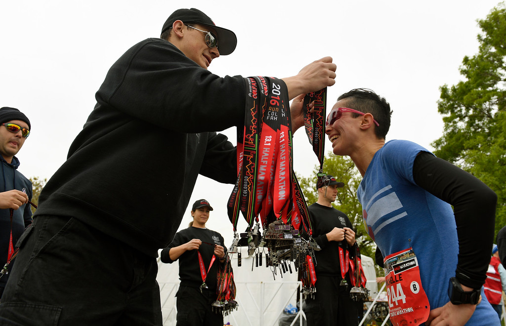 . DENVER, CO - MAY 15: West Metro Firefighter recruit Peter Neal gives runner Michelle Hughes, right, her race medal after finishing the Colfax Half Marathon during the 11th annual Colfax Half Marathon on May 15, 2016 in Denver, Colorado.  Thousands of runners took part in the annual springtime race which included a marathon, a marathon relay,  a half marathon and the urban 10 miler.  (Photo by Helen H. Richardson/The Denver Post)