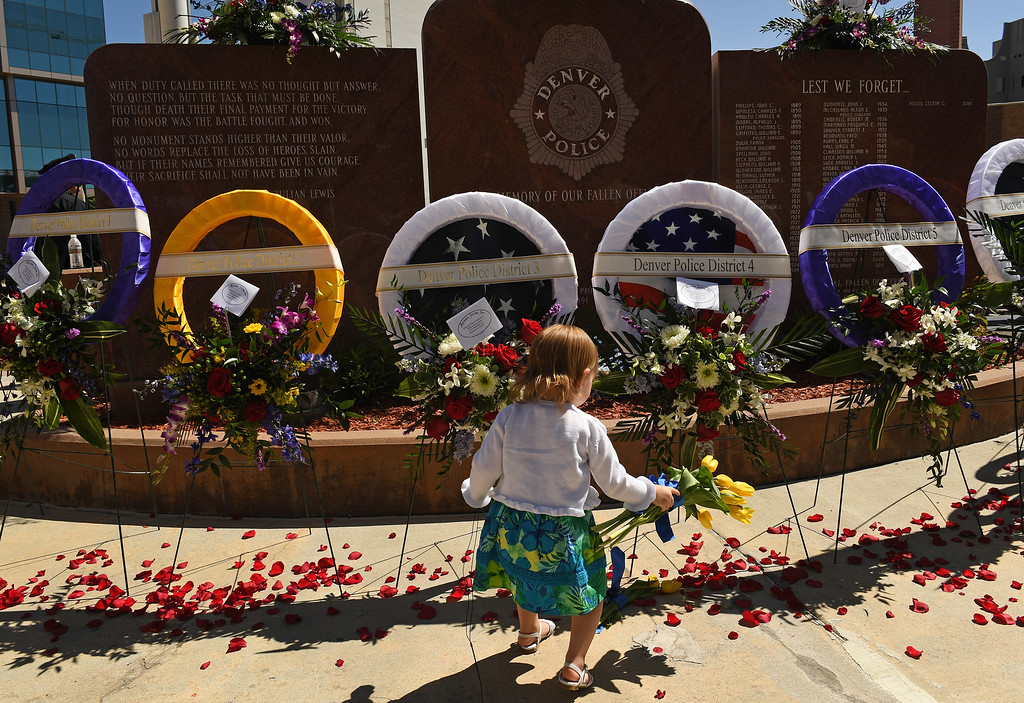 . DENVER, CO - MAY 12: Cassidy Burns, 2, places yellow tulips beneath memorial wreaths at the 24th annual Denver Police Department Memorial Service for fallen officers outside the Denver Police Department Administration Building in downtown Denver on May 12, 2016 in Denver, Colorado. Her great grandfather Denver Police officer Merle Nading died in the line of duty in 1971 and is one of the many names engraved on the Fallen Officer\'s memorial. (Photo by Helen H. Richardson/The Denver Post)
