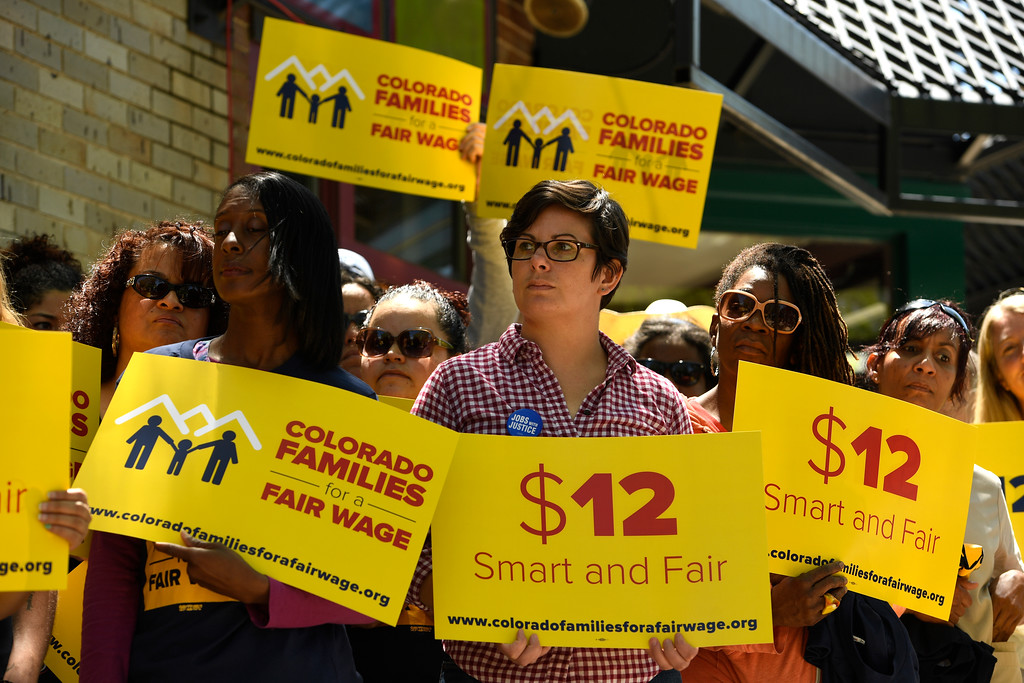 . DENVER, CO - MAY 18: People with the Colorado Families for a Fair Wage campaign hold up signs during their rally on the outdoor patio at Vine Street Pub on May 18, 2016 in Denver, Colorado.  Members from the campaign were announcing the kick off for their campaign to get a ballot initiative that would raise the state minimum wage from $6.85 to $12.00 and hour. The campaign is made up of different local non-profits as well people who would be directly impacted by the increase to the minimum wage. (Photo by Helen H. Richardson/The Denver Post)