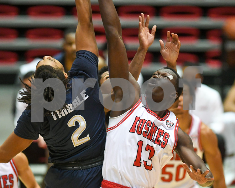 NIU center Adong Makuoi (13) goes up for a loose ball during the first half of the game while an Akron defender tries to get the ball as well during the game on Jan. 12tth.