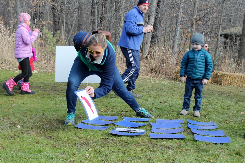 . Beckett, 4, looks on as his mom Whitney Ickes of Bainbridge tries to find a match while playing the match up at Geauga Parks Frozen Fest. (Kristi Garabrandt/The News-Herald)