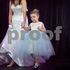 Rosemary McMahon, 4, models a flower girl dress with the assistance of Lexxus Soristo, an NIU nursing student and employee at Faranda's.