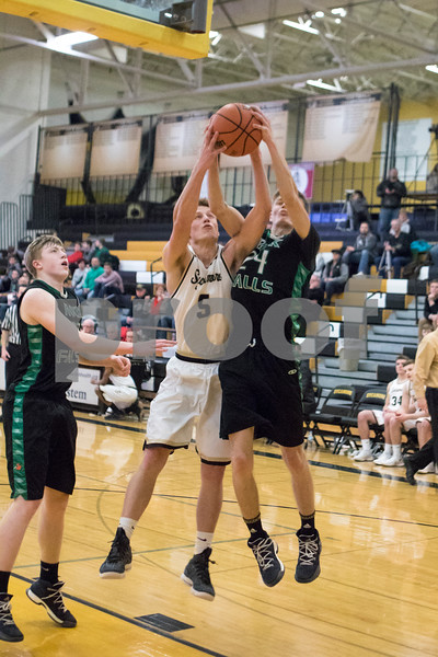 Sam Buckner for Shaw Media.<br /> Ethan Heinrich of Sycamore and Austin Meiners of Rock Falls go up for a rebound on Tuesday January 16, 2018.