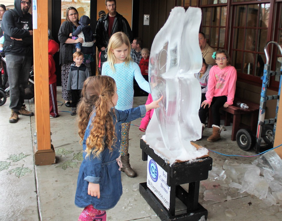 . Ellia, 3, Banbridge and Kaylee, 6, Auburn Township check out an ice carving. (Kristi Garabrandt/The News-Herald)