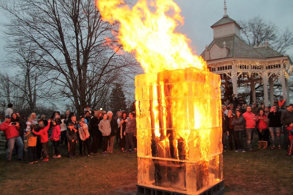 . Vistors to Chardon Winterfest gather to watch an ice tower made of wood and blocks of ice burn in the Square as a finale for Chardon\'s Winterfest. (Kristi Garabrandt/The News-Herald).