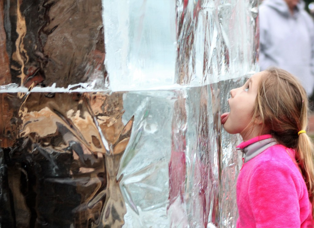 . Ava, 6, Chardon, stops to lick the ice tower before it is set ablaze at Chardon Winterfest. (Kristi Garabrandt/The News-Herald)