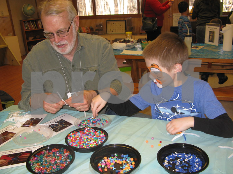Volunteer Jim Paulin helps Wilson Tull, 8, make snowflake crafts at Winterfest on Saturday at the Russell Woods Forest Preserve in Genoa.