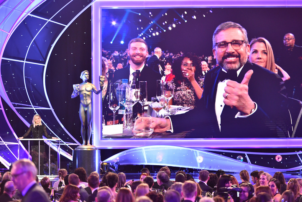 . Host Kristen Bell speaks on stage as an image of Steve Carell appears on screen at the 24th annual Screen Actors Guild Awards at the Shrine Auditorium & Expo Hall on Sunday, Jan. 21, 2018, in Los Angeles. (Photo by Vince Bucci/Invision/AP)