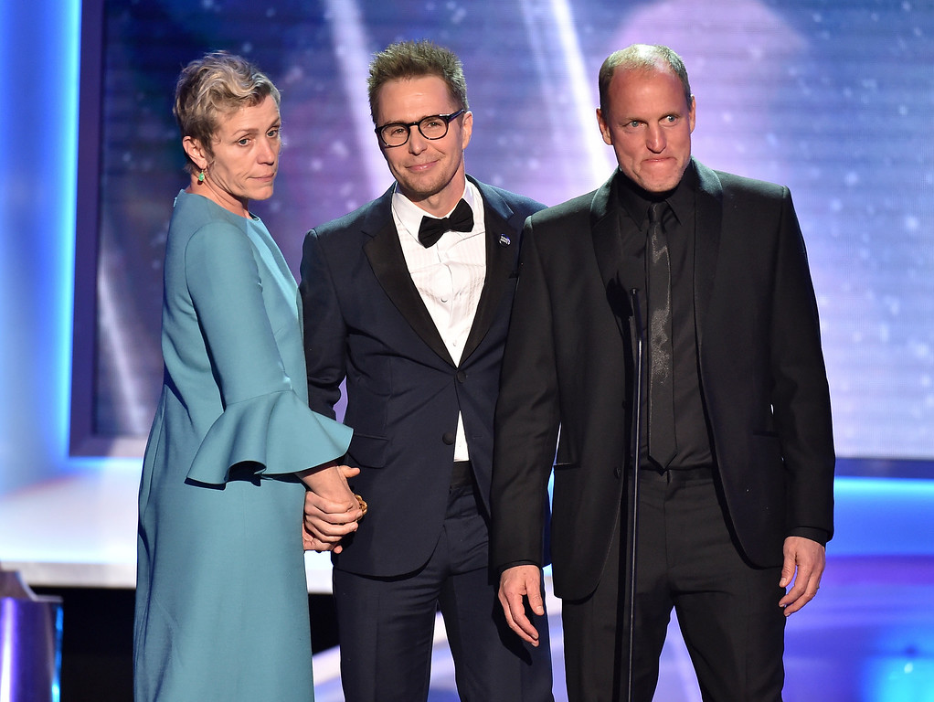 ". Frances McDormand, from left, Sam Rockwell and Woody Harrelson, nominees for outstanding performance by a cast in a motion picture for ""Three Billboards Outside Ebbing, Missouri,\"" introduce a clip from their film at the 24th annual Screen Actors Guild Awards at the Shrine Auditorium & Expo Hall on Sunday, Jan. 21, 2018, in Los Angeles. (Photo by Vince Bucci/Invision/AP)"