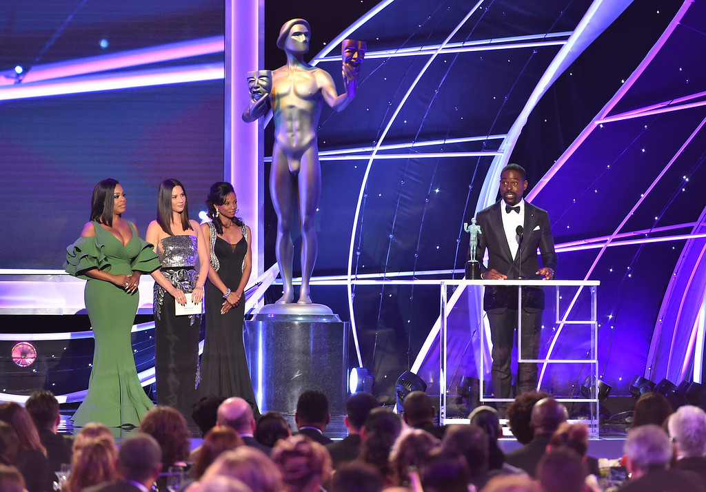 ". Sterling K. Brown accepts the the award for outstanding performance by a male actor in a drama series for ""This Is Us\"" as presenters Niecy Nash, left, and Olivia Munn, second left, look on at the 24th annual Screen Actors Guild Awards at the Shrine Auditorium & Expo Hall on Sunday, Jan. 21, 2018, in Los Angeles.  (Photo by Vince Bucci/Invision/AP)"