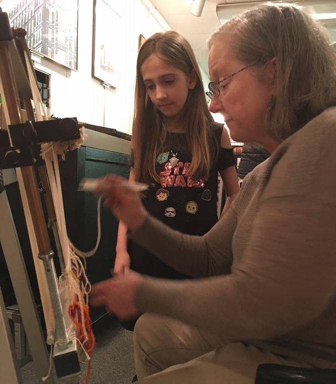 . Richard Payerchin - The Morning Journal <br> Jovie Sedlick, 7, of Avon Lake, watches as weaver Peggy Strang of Avon works at the tapestry loom at the Jan. 20, 2018, grand opening of the TrueNorth Cultural Arts center at 739-1 Moore Road, Avon Lake. Arts enthusiasts packed the open house on Jan. 20, 2018, to celebrate the opening and tour the new center. Strang will be an artist in residence for weaving.