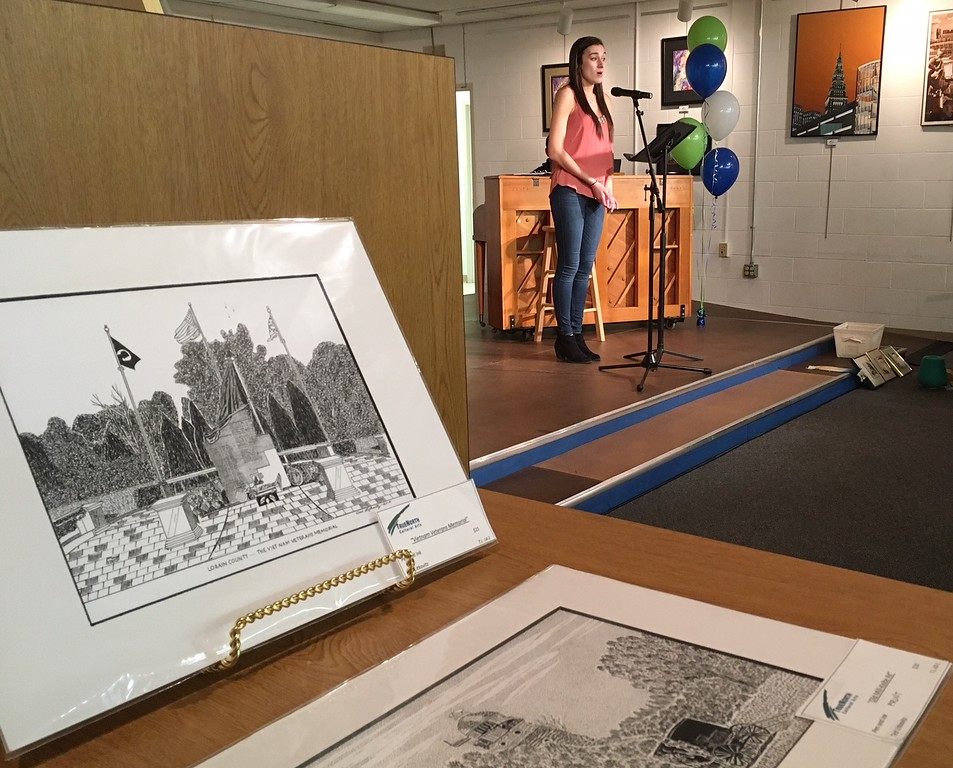. Richard Payerchin - The Morning Journal <br> Prints by artist Ted Litkovitz sit in the foreground as Tia Karaplis sings during the grand opening of TrueNorth Cultural Arts\' new artistic center at 739-1 Moore Road, Avon Lake. Arts enthusiasts packed the open house on Jan. 20, 2018, to celebrate the opening and tour the new center.
