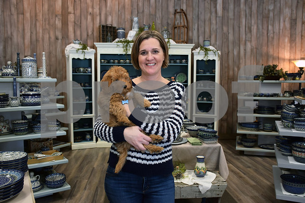 """Rebecca Gengler, owner of More Polish Pottery LLC, holds her 9-week-old Goldendoodle puppy named Bear while standing in the new showroom of her shop. More Polish Pottery, located at 8S953 Jericho Road in Big Rock, will celebrate its """"re-grand opening"""" from Jan. 24 to 31with open house-style events, including presentations, food, tours and special deals."""