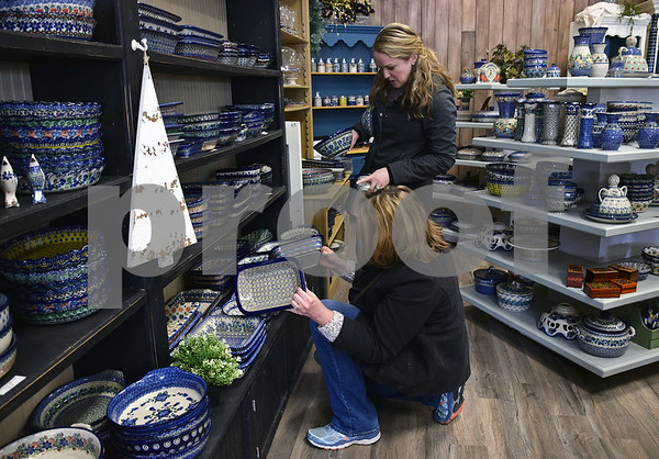 On Tuesday, Jan. 16, Mary Vacey of Orland Park kneels while her daughter Hannah Riessen of Lockport helps her decide which bowl of Polish pottery to purchase during their first time shopping at More Polish Pottery in Big Rock.