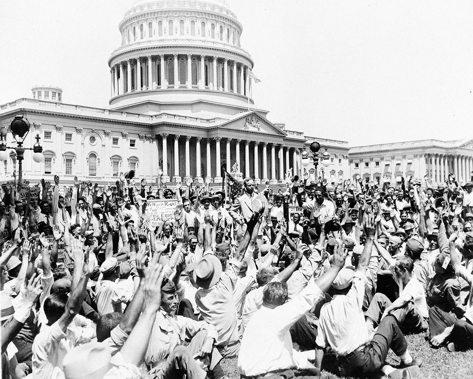 . Brigadier Gen. Pelham D. Glassford, superintendent of the Washington, D.C., police, got this response when he asked a group of war veterans on the Capitol grounds to raise their hands if they had served in France and were one hundred percent American, July 13, 1932.  Glassford, now retired, was there as an army officer.  The veterans were at the Capitol urging immediate payment of the soldiers\' bonus.  Left to right at center: Glassford and Roy W. Robertson, leader of a California group.  (AP Photo)
